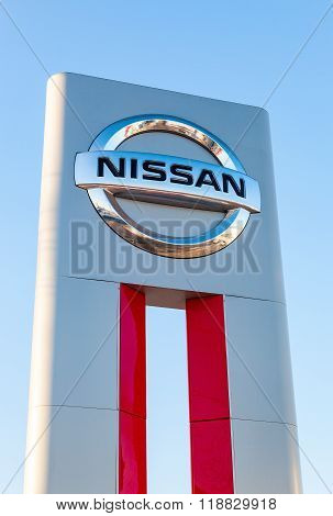 Official Dealership Sign Of Nissan Against Blue Sky