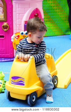 POZNAN POLAND - FEBRUARY 20 2016: Two years old child sitting on a toy car in a play room