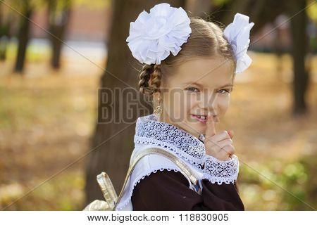 Portrait of attractive girl with finger on lips, concept of student show quiet, silence, secret gesture, young schoolgirl in a festive school uniform on the background autumn park