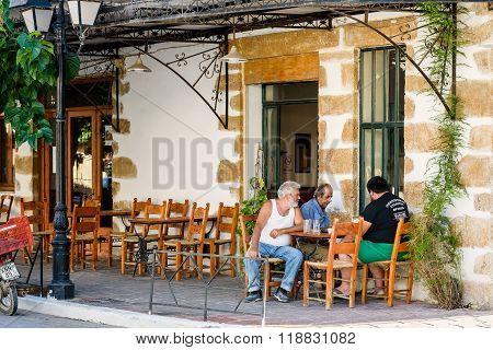 Three old men sitting at greek taverna and playing backgammon