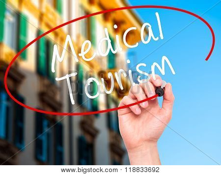 Man Hand Writing Medical Tourism With Black Marker On Visual Screen