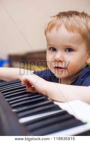 Small Boy Enjoys Playing Electric Piano (synthesizer)