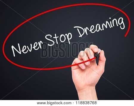 Man Hand Writing Never Stop Dreaming With Black Marker On Visual Screen