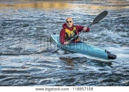 senior male paddling a whitewater kayak on a turbulent river