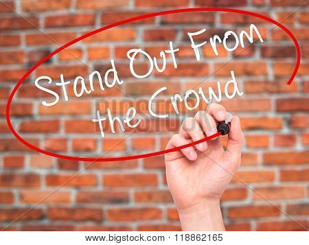 Man Hand Writing Stand Out From The Crowd With Black Marker On Visual Screen