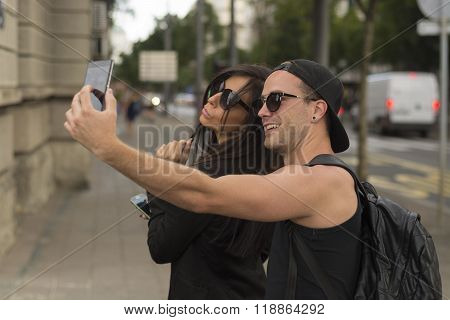 Young cheerful friends taking photos of themselves on smart phone urban city outdoor scene selective focus