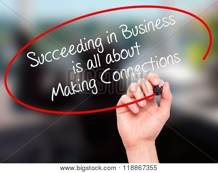Man Hand Writing Succeeding In Business Is All About Making Connections With Black Marker On Visual