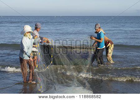 Fishermen with nets on the shore. Danag, Vietnam