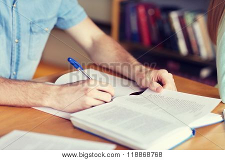 people, learning, education and school concept - close up of student boy hands with book or textbook writing to notebook at library