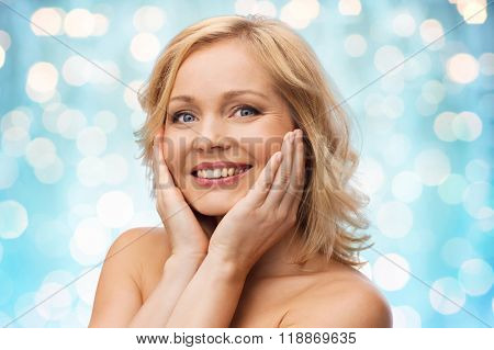 beauty, people and skincare concept - smiling woman with bare shoulders touching face over blue holidays lights background
