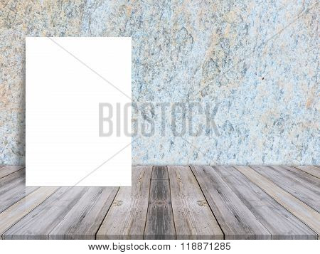Blank white poster leaning at tropical wood table top with dark stone wall. Mock up background for adding content