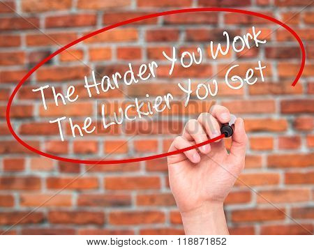 Man Hand Writing The Harder You Work The Luckier You Get  With Black Marker On Visual Screen