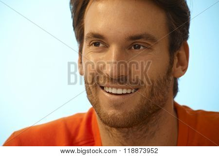 Portrait of happy handsome casual caucasian man with stubble. Smiling, perfect teeth, copyspace.
