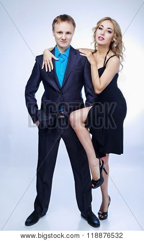 confident young man and a beautiful blond woman, seducing him, against blue studio background