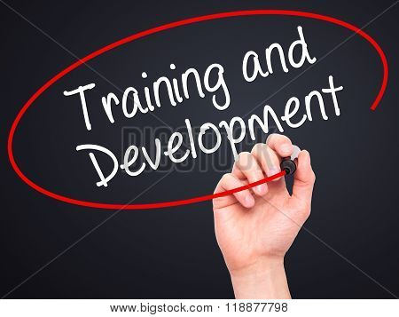 Man Hand Writing Training And Development With Black Marker On Visual Screen