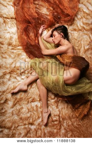 Beautiful woman sleeping covered in silk