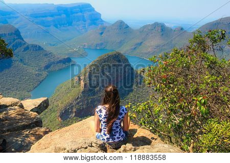 Girl sitting on stone on the cliff