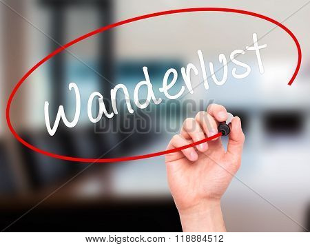 Man Hand Writing Wanderlust With Black Marker On Visual Screen