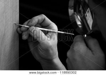 Restorer's hands with magnifying glass and brush