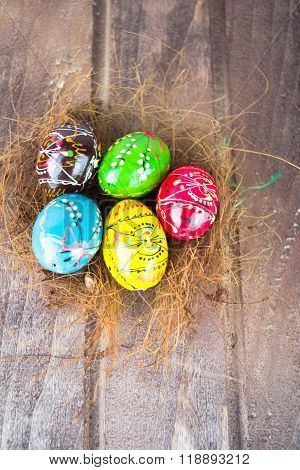 Colorful easter eggs in straw nest on a wooden table