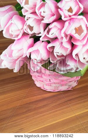 Pink tulips in a basket over shabby wooden background