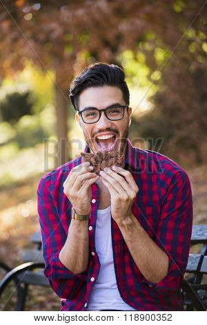 Young man eating a cookie, looking happy at the camera. Hipster style, wearing a check shirt