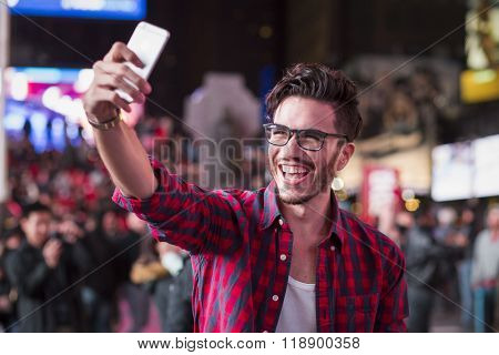 Man taking a selfie on Times Square, New York, at night in autumn