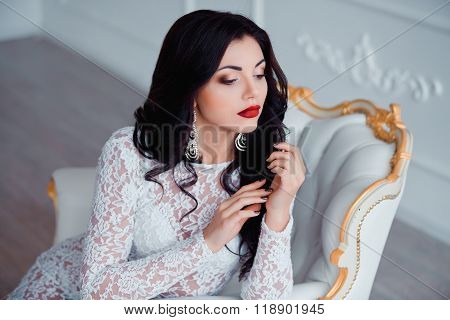 Portrait of perfect, sexy young woman with long black hair and red lips wearing seductive white dres
