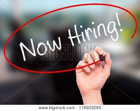 Man Hand Writing Now Hiring! With Marker On Transparent Wipe Board