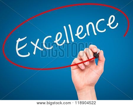 Man Hand Writing Excellence With Marker On Transparent Wipe Board Isolated On Blue