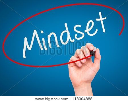 Man Hand Writing Mindset With Marker On Transparent Wipe Board Isolated On Blue