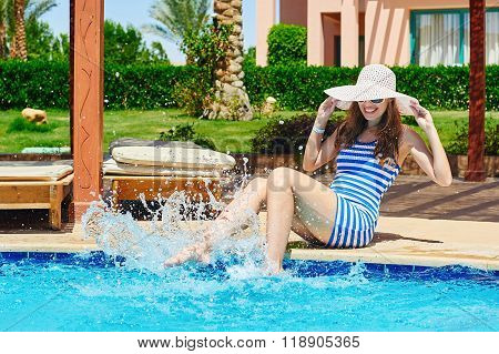 Young beautiful woman enjoying the sun and sitting on edge of pool