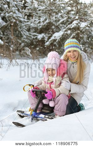mother and daughter with  snowmobile