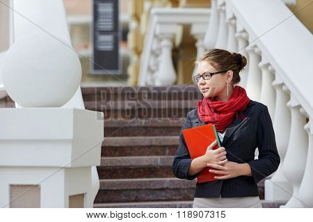 Closeup portrait of pretty young student girl holding exercise books and folder