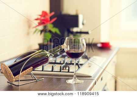 Glass Of Red Wine With Bottle On Kitchen Worktop