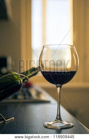 Glass Of Red Wine With Bottle On The Kitchen Table