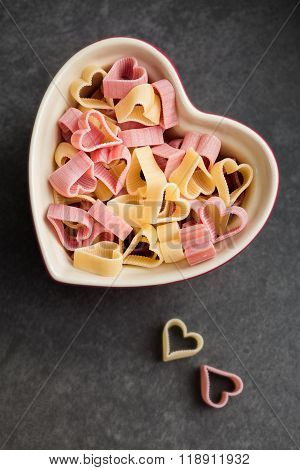 Red And Yellow Heart Shaped Pasta In Heart Shape Ramekin, Top View, Food Background