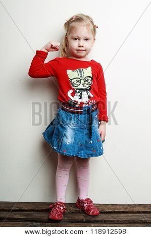 Little Cute Blonde Girl In A Red Shirt And A Jeans Skirt