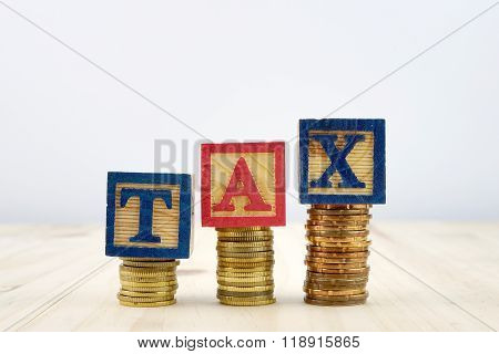 Tax Concept With Wooden Blocks On Stacked Of Coins Against White Background
