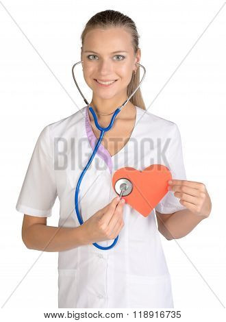 Woman cardiologist listens paper heart in hand