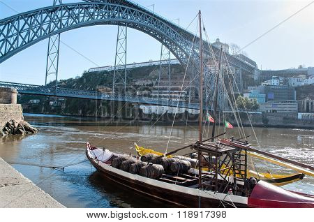 The Dom Luis I Bridge Over The Douro River With Rabelo Boats. Porto, Portugal
