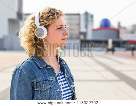 Hipster teen girl smiling and listening to music in city