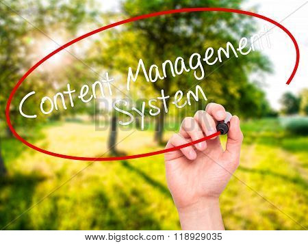 Man Hand Writing Content Management System  With Black Marker On Visual Screen
