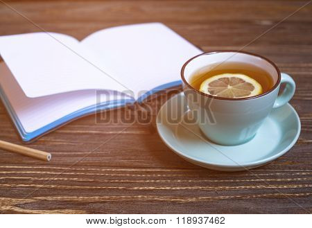Hot tea with lemon and notebook on wood background - seasonal relax concept