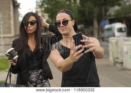 Cheerful friends taking photos of themselves on smart phone, urban city outdoor scene, selective focus