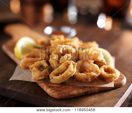 fried calamari rings on wooden tray with dipping sauce