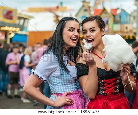 Two young women in Dirndl dress or tracht, laughing with cotton candy floss at the Oktoberfest