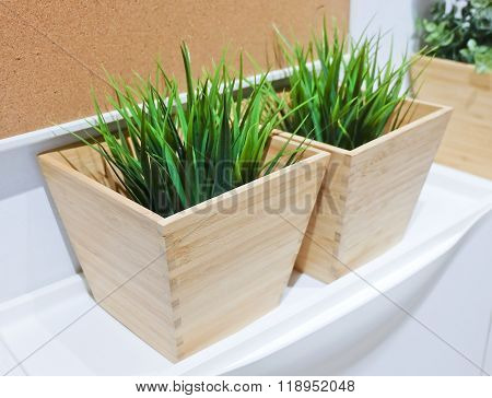 Two Green Artificial Plant In A Wooden Pot