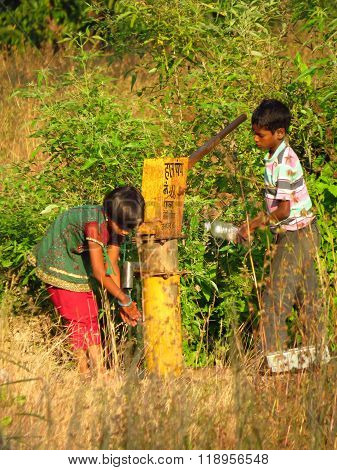 Pune, India - November 20, 2013: Two Indian Children Try To Get Some Water Using The Hand Pump In Th