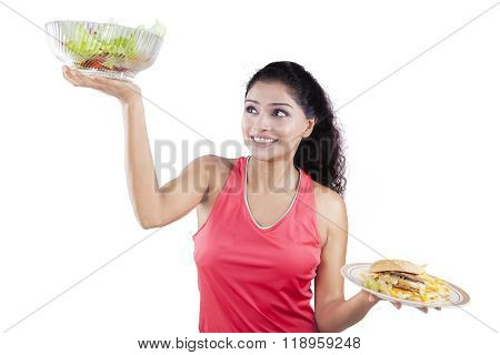Woman Lifting Healthy Food And Fast Food